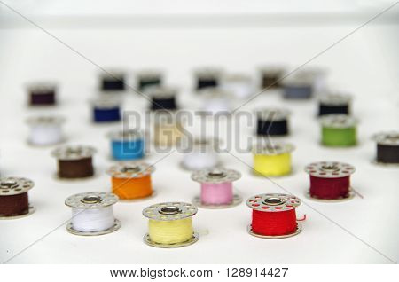 Metal bobbin spools with colorful thread arranged in white background