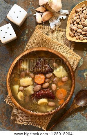 Traditional Hungarian Babgulyas (bean goulash) a soup made of pinto beans smoked meat potato carrot csipetke (homemade soup pasta) garlic onion served in wooden bowl photographed overhead on slate with natural light