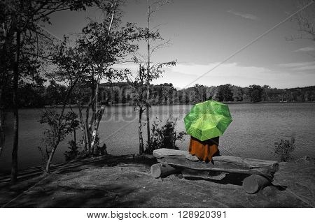 A woman sitting on the lake shore with green umbrella