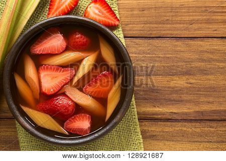 Warm or cold fruit soup made of strawberry and rhubarb served in rustic bowl photographed overhead on dark wood with natural light
