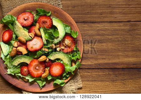 Strawberry avocado lettuce salad with cashew nuts on plate photographed overhead on dark wood with natural light