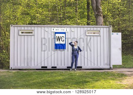 Woman keeping her nose with two fingers at a public toilet with sign WC in the city park in a summer time