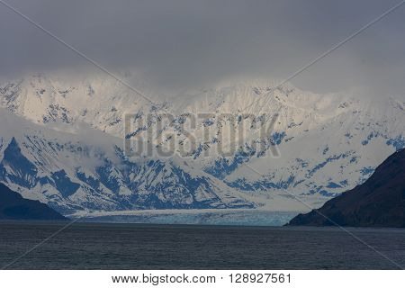 A dramatic photo of a glacier with snow-capped moiuntains in the background