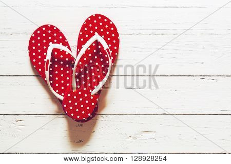 Beach flip flops on white wood floor Summer essential items Heart shape of flip flops on wood floor