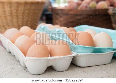 Fresh local eggs in a carton at the farmers market.
