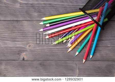 Color pencils and black office bin on dark wooden background