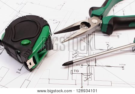 Metal pliers screwdriver and tape measure on electrical construction drawing of house work tools and drawing for projects engineer jobs concept of building house