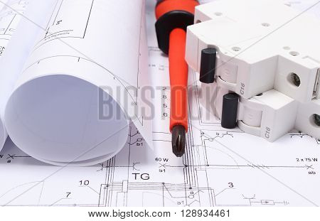 Rolls of electrical diagrams electric fuse and work tools lying on construction drawing of house drawings for the projects engineer jobs
