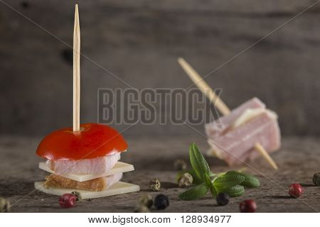 Mini ham and cheese appetizer with tomato and spices over wooden background