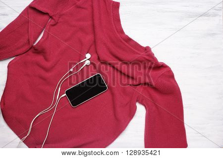 Top view of young woman's pink sweater on white wooden background with a smarphone and earplugs. Copyspace.