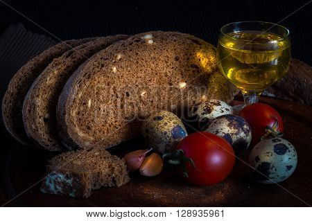 Fresh bread on wooden tablevintage filter Traditional black rye-bread on dark background Red cherry tomatoes with sliced bread and quail eggs and glass of olive oil vintage still life