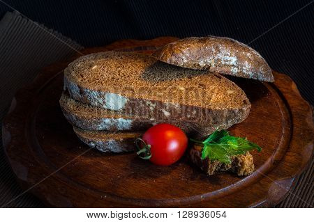 Fresh bread on wooden tablevintage filter Traditional black rye-bread on dark background Red cherry tomatoes with sliced bread vintage still life