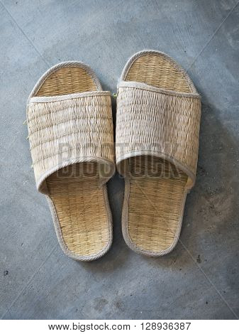 Woven slippers on Cement floor in room