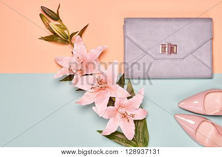 Fashion woman accessories set. Glamor shoes, stylish handbag clutch and summer lily flowers. Elegant trendy girl. Unusual creative look. Overhead, romantic. Top view, vanilla pastel background