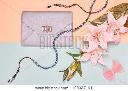 Glamor shoes, stylish handbag clutch and summer lily flowers. Fashion woman accessories set. Elegant trendy girl. Unusual creative look. Overhead, romantic. Top view, vanilla pastel background