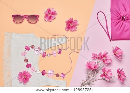 Summer Fashion woman clothes accessories set. Glamor lace top, stylish necklace, handbag clutch, sunglasses, pink flowers. Unusual creative elegant look. Overhead, romantic.Top view, yellow background