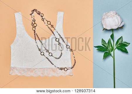 Fashion woman clothes accessories set. Glamor lace top, stylish necklace and summer white flower. Elegant trendy outfit. Unusual creative girl. Overhead, romantic. Top view, vanilla pastel background