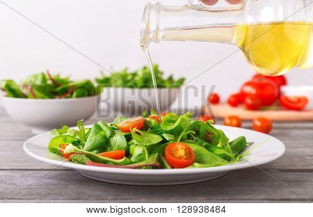 Olive oil pouring from a glass carafe in the Italian salad fresh leaves of chard arugula and cherry tomatoes. Healthy eating and diet concept