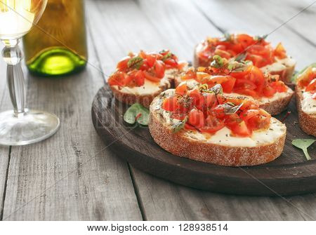 Sandwich with tomatoes goat cheese and basil on a wooden table with a glass of white wine with copy space. Tasty appetizer wine