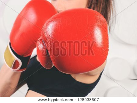 Woman boxer hit straight at the camera focus on boxing gloves. Woman boxer fist close up