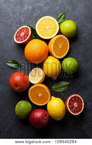 Fresh ripe citruses. Lemons, limes and oranges on dark stone background. Top view