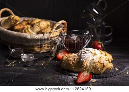 Fresh almond croissants strewing by sugar powder, vintage style.