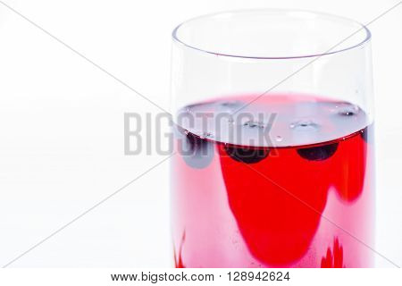 Macro shot of alass of aronia juice with berries in the light background