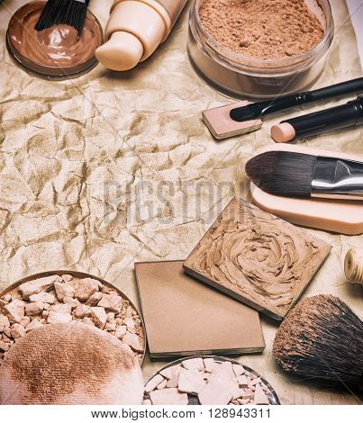 Various makeup products to even out skin tone and complexion laid out as semicircular frame on aged paper. Copy space. Retro style processing