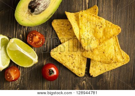 Corn tortilla chips Nachos and Guacamole sauce ingredients on wooden table. Top view