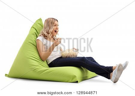 Woman watching something seated on a green beanbag and laughing isolated on white background