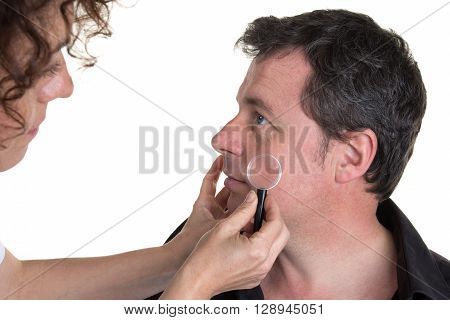 Serious Doctor Examining Pigmented Skin With Dermatoscope
