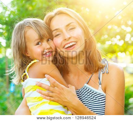 Beautiful Mother And her little daughter outdoors. Nature. Beauty Mum and her Child playing in Park together. Outdoor Portrait of happy family. Joy. Mom and Baby