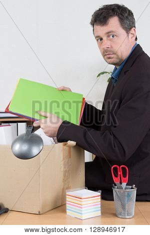 Unshaven And Tired Businessman Putting His Staff In The Box