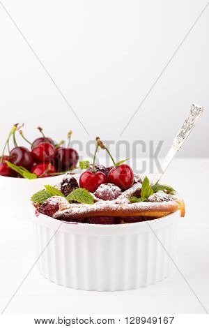French clafoutis with cherry in ceramic ramekins on white wooden table