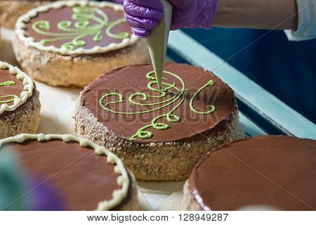 Brown cakes with green ornament. Worker's hand decorating a cake. Putting cream on cake's surface. Standard of quality.