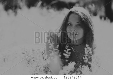 Young brunette woman in a white dress. A girl sits in the middle of flowers field on a sunny day. Field flowers beauty nature - The concept of country vacation. Article about vacation.
