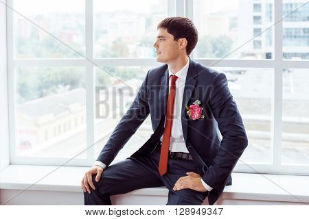 Gorgeous smiling groom. Handsome man in a suite with a buttonhole sitting on window sill indoors