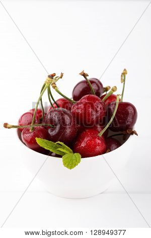 Red ripe cherries in a white bowl on white wooden background