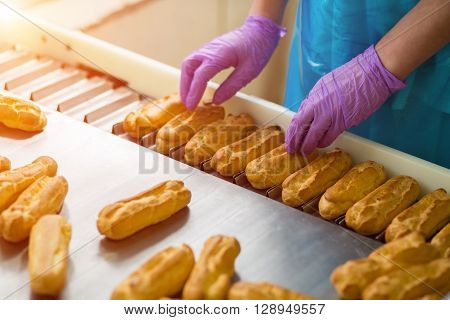 Hands in gloves touching eclairs. Eclair shells on narrow conveyor. Employee of confectionery plant. Worker responsible for quality.