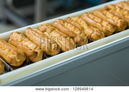 Baked products on conveyor belt. Narrow conveyor with eclair shells. Single standard of shape. Food manufacturing at the plant.