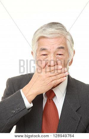 senior Japanese businessman making the speak no evil gesture