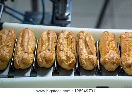 Conveyor line with eclairs. Baked pastry laying on conveyor. Dessert with cream filling. Crispy food produced at factory.