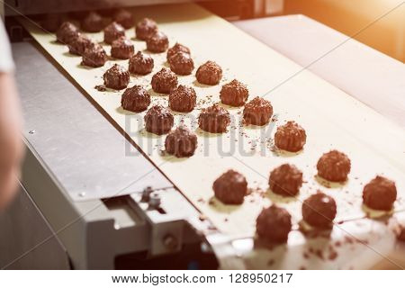 Dark brown sweets with shavings. Dark candies on beige cloth. Sweet product of quality chocolate. Production of tasty dessert.