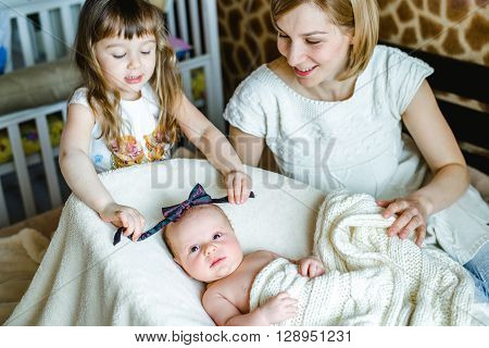 Young mom with her 5 years old daughter and 2 months old baby and playing in the bed at the weekend together