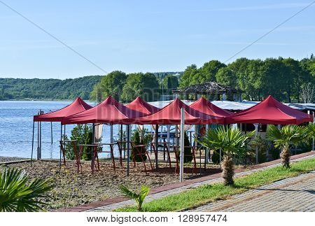 Cafeteria with chairs and red parasols by the lake in a sunny day