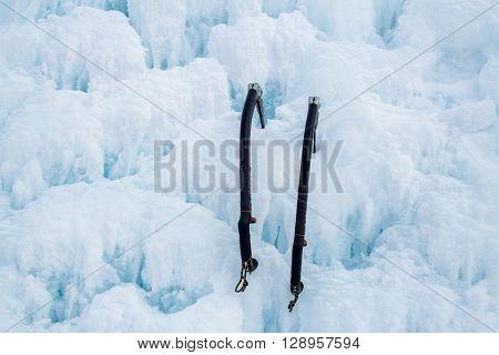 Pair of ice axes on blue wavy ice