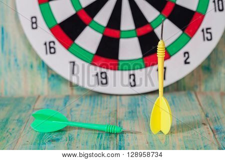green and yellow  dart arrow and dartboard