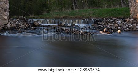 the threshold of stones on the river on the background of green grass
