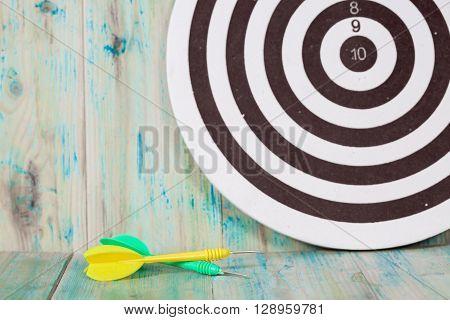 green and yellow dart arrow on dartboard