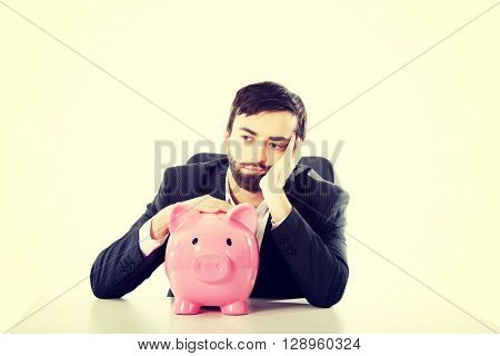 Businessman with piggybank by a desk.
